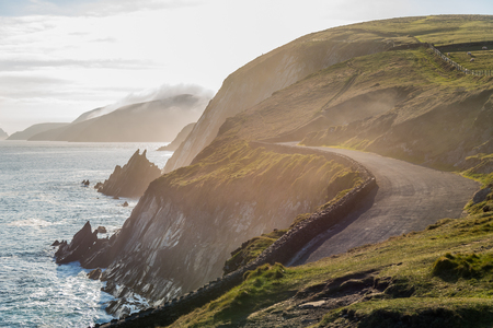 Narrow Irish costal road in spring evening, just above the steep and dangerous cliffs. Stock Photo