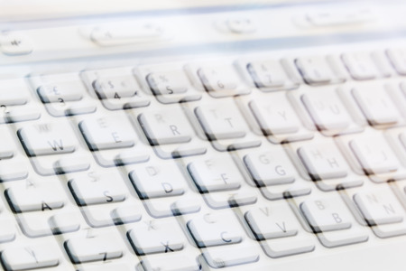 lates: Double Exposure of a white portable keyboard. Concept of unclear communication, or dangers of modren communication.