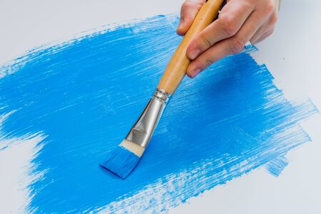 painter: Hobby artist painting with blue acrylic paint on white foam board
