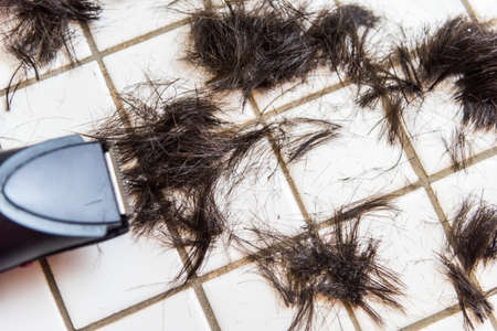 black barber: A photo of a trimmed hair on the white tiled floor with the trimming machine Stock Photo