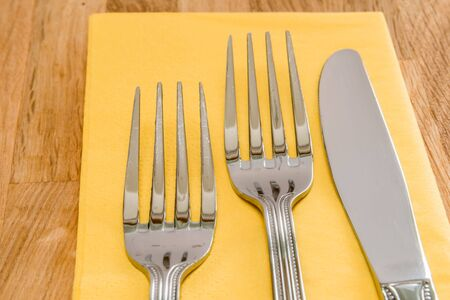 serviette: Dinner cutlery served on a yellove serviette on wooden background. Stock Photo