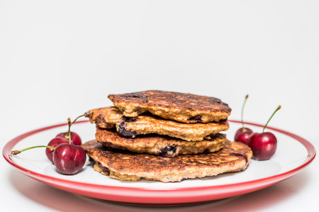 gestational: Home made buckwheat pancakes piled on a plate with sweet cherry. Healthy option to cheat gestational diabetes. Stock Photo