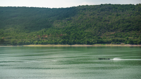 amongst: Fishing boat in calm waters amongst mountain Stock Photo