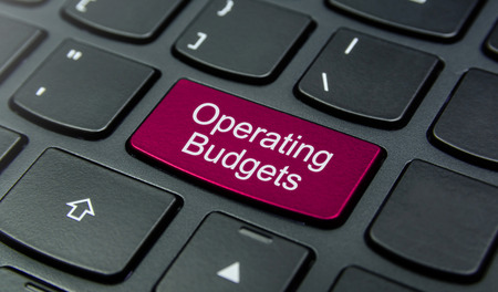 budgets: Close-up the Operating Budgets button on the keyboard and have Magenta color button isolate black keyboard Stock Photo