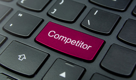 competitor: Close-up the Competitor button on the keyboard and have Magenta color button isolate black keyboard Stock Photo