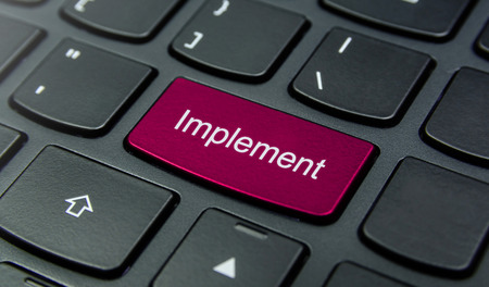 implement: Close-up the Implement button on the keyboard and have Magenta color button isolate black keyboard Stock Photo
