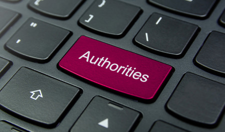 authorities: Close-up the Authorities button on the keyboard and have Magenta color button isolate black keyboard Stock Photo