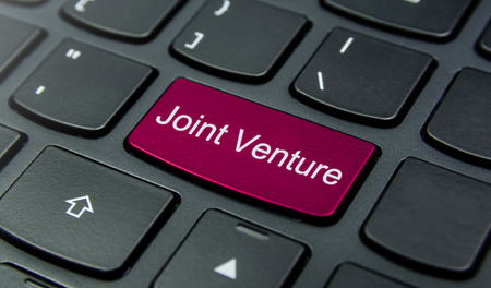 joint venture: Close-up the Joint Venture button on the keyboard and have Magenta color button isolate black keyboard Stock Photo