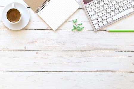 mesa de escritório com bloco de notas, teclado de computador e copo de café.