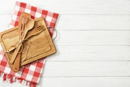 cuillères en bois et autres ustensiles de cuisine avec des serviettes rouges sur la table de cuisine.