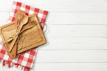 Wooden spoons and other cooking tools with red napkins on the kitchen table.