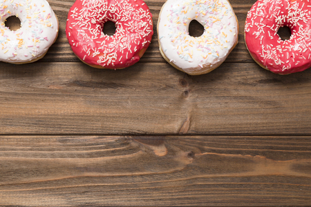 delicious sweet donuts on the wooden background. Stock Photo