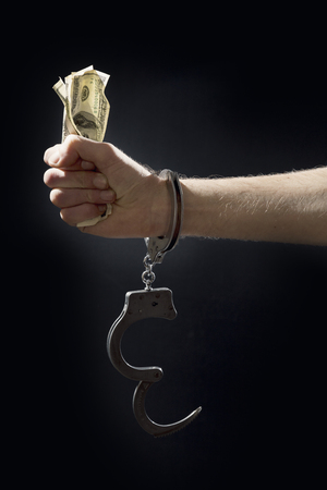 bank robber: Man in handcuffs with money. Stock Photo