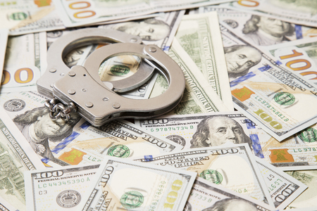 part prison: handcuffs with money on the table