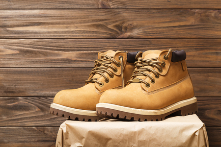 new leather boots on wooden background.