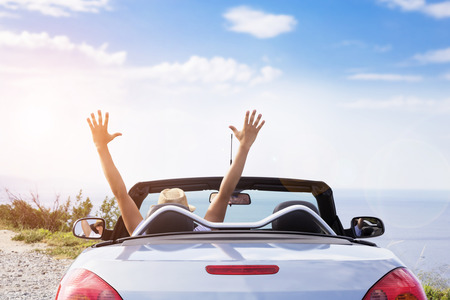 Young men drive a car on the beach.