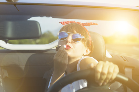 Young woman driving a car on the beach. Stock Photo