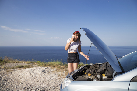 A woman repair the car, her car broke down on the road side. Stock Photo