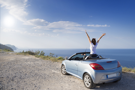 Young woman drive a car on the beach. Stockfoto