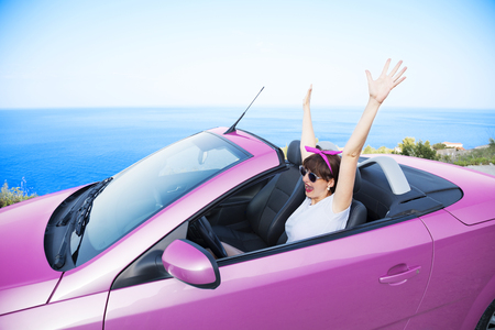 Young woman drive a car on the beach. Stock Photo