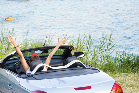 Young woman drive a car on the beach. Banque d'images