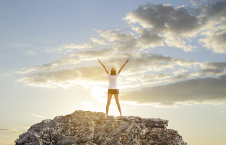 standing stone: Happy woman with hands up standing on cliff over sea and islands at sunset. Stock Photo