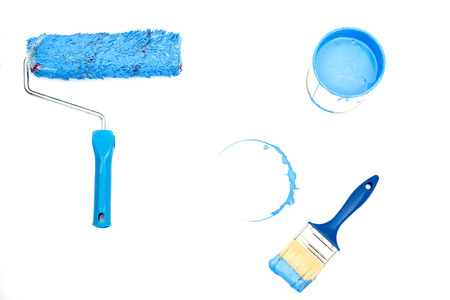 open, painted bucket , roller ,  and paintbrush on a white backdrop. Stock Photo