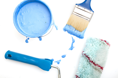 open, painted bucket , paint roller and paintbrush on a white backdrop. Standard-Bild