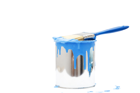 open, painted bucket and paintbrush on a white backdrop.