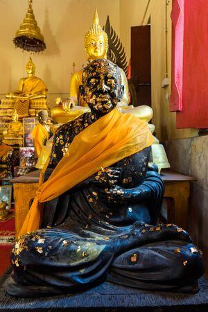 buddism: Sitting Black Buddha statue with gold leaf Editorial