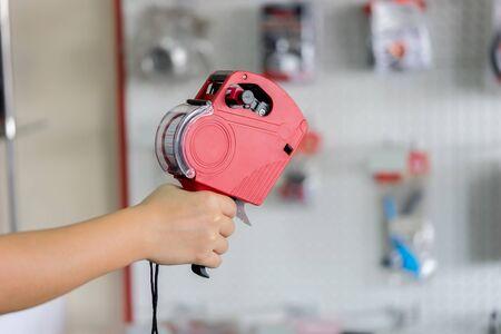merchandise mart: Hand holding shop pricing gun Stock Photo