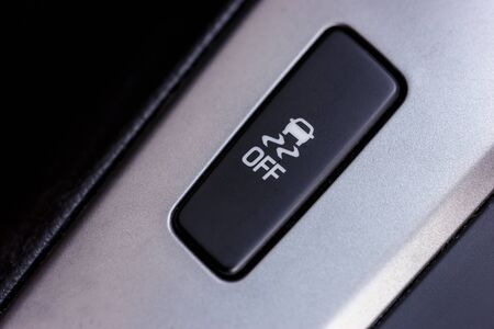 traction: Slippery button. An image of a button for traction control in a modern car