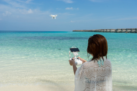 remote controls: woman with remote controller, controls a flying drone at the sea