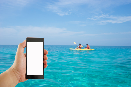 'rock drill': hand holding mobile phone on lady paddling the kayak blur background Stock Photo