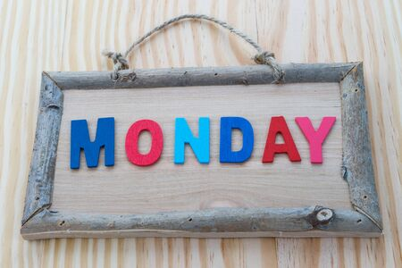 weekdays: Monday word with colorful letter on Wood Background
