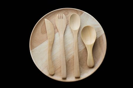 close up wooden dish ,spoon,fork and knife on black background. top view
