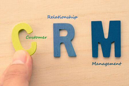 Hand arrange letters as CRM (Customer , Relationship , Management)