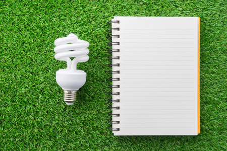 Orange notebook and lamp on green grass. Stock Photo