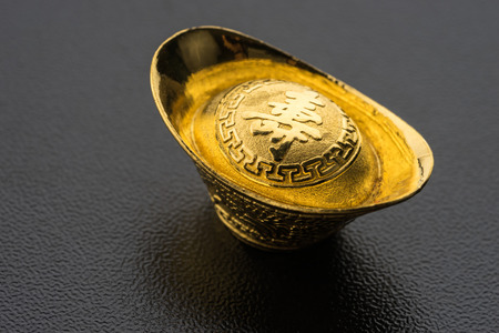 Closeup of big gold on black background. Chinese word mean wealthy Stock Photo