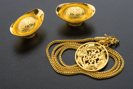 goldmine: Closeup of big gold on black background. Chinese word mean wealthy and lucrative