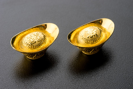 constancy: Closeup of big gold on black background. Chinese word mean wealthy and lucrative