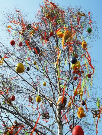 Tree decorated Easter eggs and confetti under a blue sky. photo