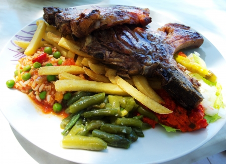 repast: Roasted veal chops with fries and vegetables in Croatian restaurant