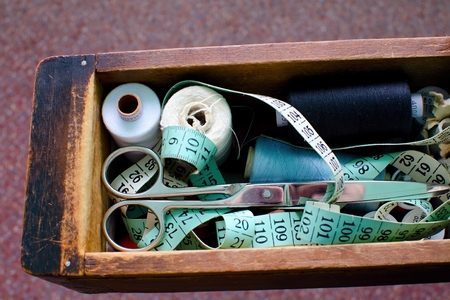 Socket with sewing kit in which scissors, thread and tape measure  photo