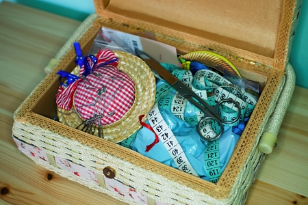 sewing box: Supplies for sewing in a beautiful box on pine table. Stock Photo