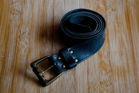 waistband: Old black and scuffed leather belt on a wooden table.