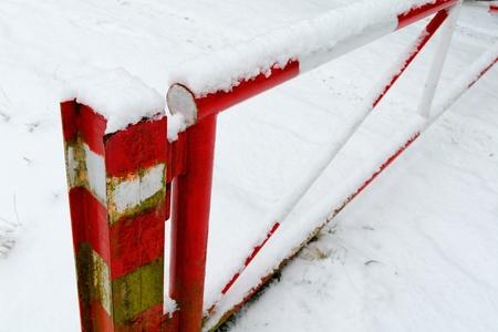 rejas de hierro: Rojo y blanco barrera de nieve primera nieve de este a�o. Foto de archivo