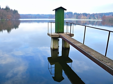 floodgates: Footbridge with booth with a mechanism floodgates on a pond.