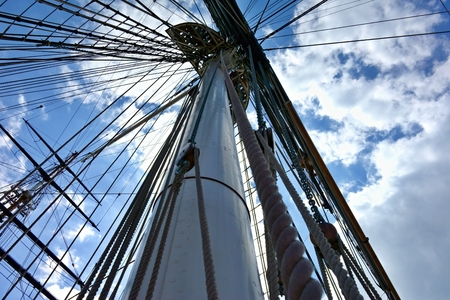 Historic sailboat mast with boom and know the ropes with a sky background.