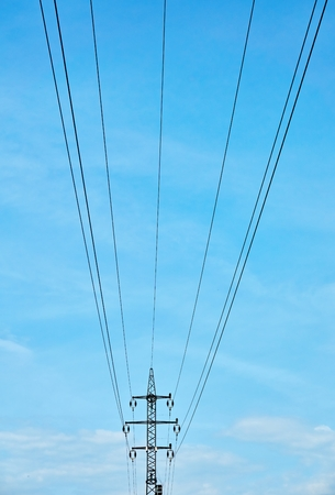 High voltage power mast against the blue sky from the ceiling.                                Stock Photo
